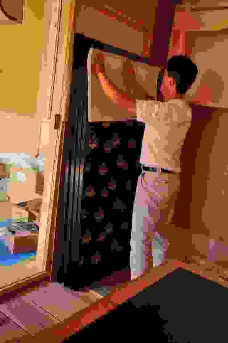 和紙を宛がい手のひらで下張和紙に圧着させる作業 モダンな 窓&ドア の 樹・中村昌平建築事務所 モダン
