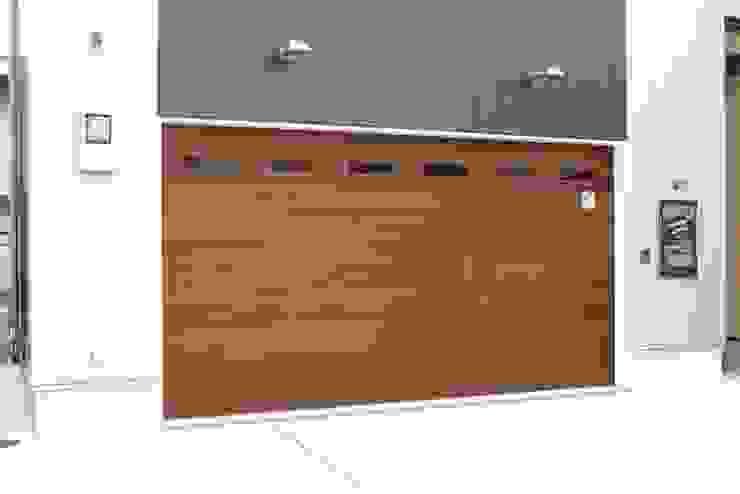オーバーガレージドア 米杉フラットタイプ パスドア付: 株式会社ワールドガレージドアが手掛けた現代のです。,モダン