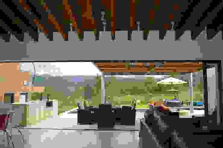 Vista desde la estancia hacia el exterior. El cancel corredizo permite la integración total de la terraza con la estancia. Balcones y terrazas de estilo moderno de Revah Arqs Moderno