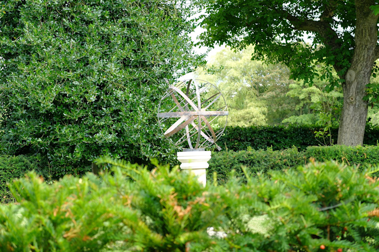 Verdigris armillary behind an evergreen hedge de Border Sundials Ltd Clásico