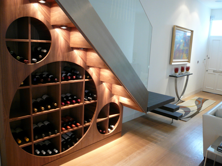 Wine cellar beneath contemporary staircase Bodegas modernas de Space Alchemy Ltd Moderno