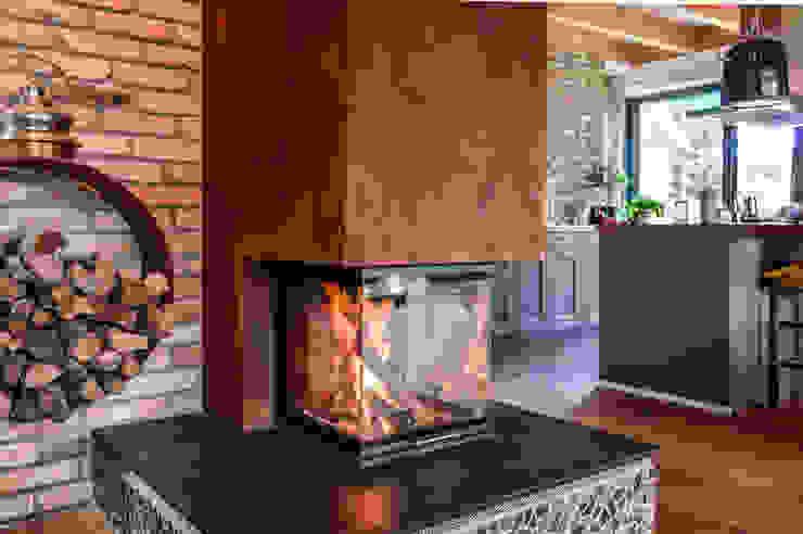 Kamin mit dreiseitiger Verglasung in Rostoptik, Wand aus alten Klinkersteinen Moderne Wohnzimmer von architektur. malsch - Planungsbüro für Neubau, Sanierung und Energieberatung Modern