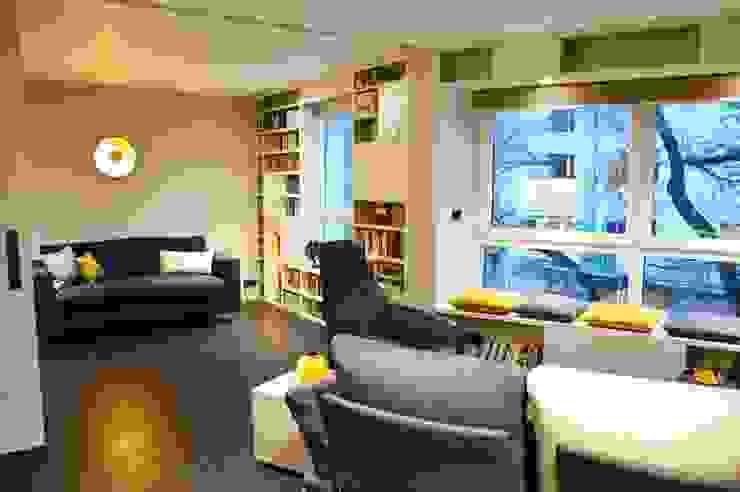 Salon avec une bibliothèque sur façade et une porte coulissante télescopique pour séparer les espaces Salon moderne par Agence MIND Moderne