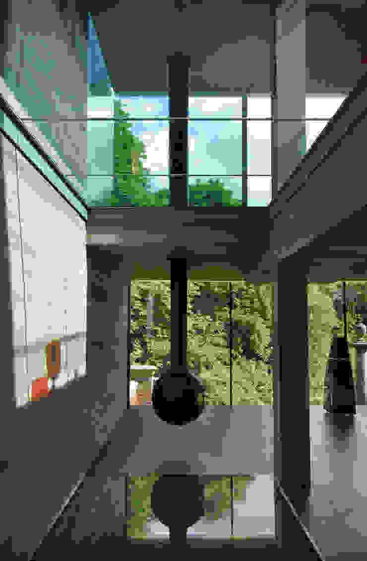 Hanging fireplace, glass floors, concrete structure and view to cemetery Livings de estilo minimalista de Eldridge London Minimalista