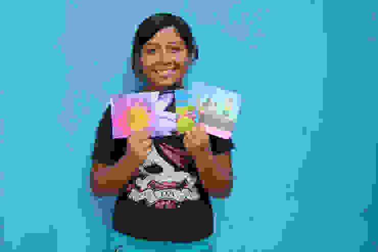 FairMail fotografe Yomira (18) laat haar fair trade kaarten zien. van FairMail Tropisch
