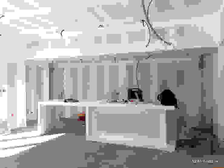 Chantier - L'îlot de cuisine en plâtre, achevé, délimite les usages de l'espace de vie. par 3B Architecture Moderne