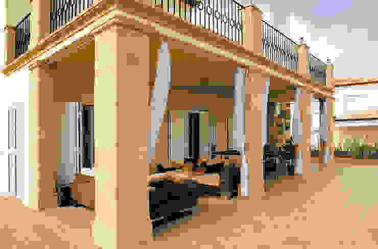 Porche con columnas de tosca de Artosca Moderno