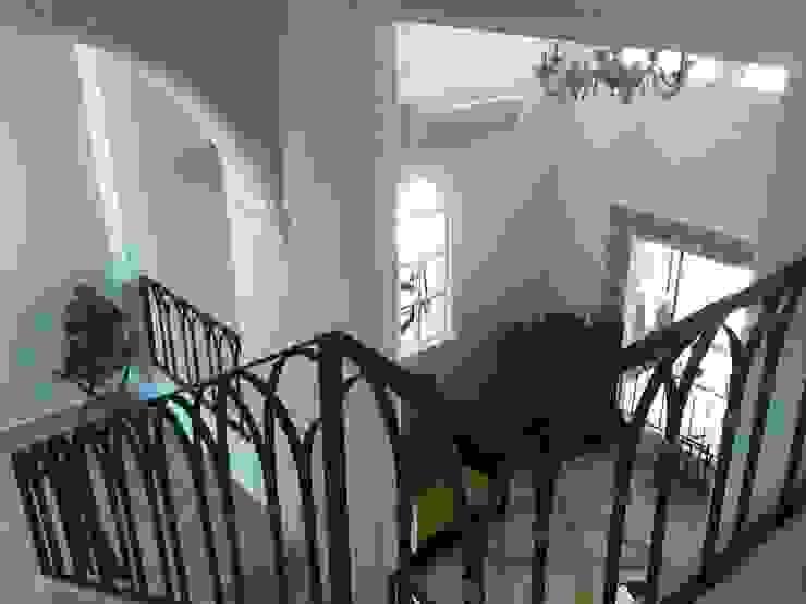 Estancia vista desde el vestíbulo de acceso después de la remodelación de ARQUELIGE Rústico