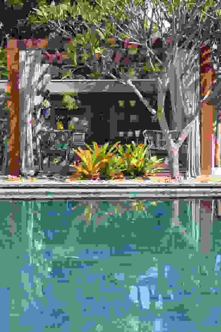 Detalhe da luz ao incidir na piscina Piscinas tropicais por RABAIOLI I FREITAS Tropical Pedra