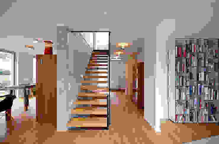 schwebende Treppenstufen an einer Sichtbetonwand mit Glasabtrennung Moderner Flur, Diele & Treppenhaus von Marcus Hofbauer Architekt Modern