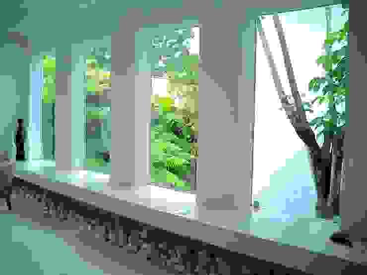 Bancada do ambiente social rodeada por jardim tropical Portas e janelas minimalistas por Kika Prata Arquitetura e Interiores. Minimalista