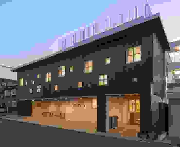 夜は田の字型の窓が壁面に浮かびあがる。 モダンな 家 の フィールド建築設計舎 モダン 木 木目調