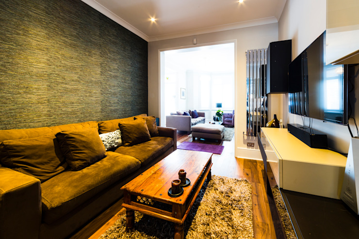 Living room with seaweed green feature wall and wooden floors من Affleck Property Services حداثي