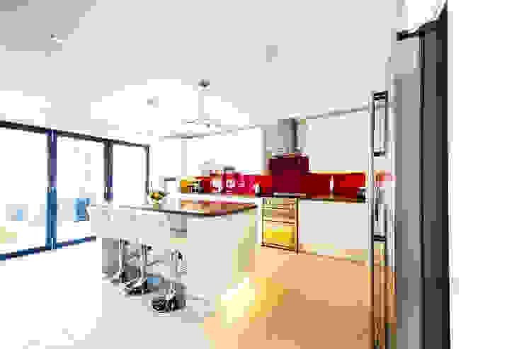 White kitchen with red splashback, modern kitchen pendants, and bifold doors من Affleck Property Services حداثي