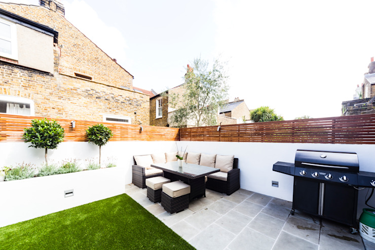 Garden with black and white furniture and fake grass من Affleck Property Services حداثي
