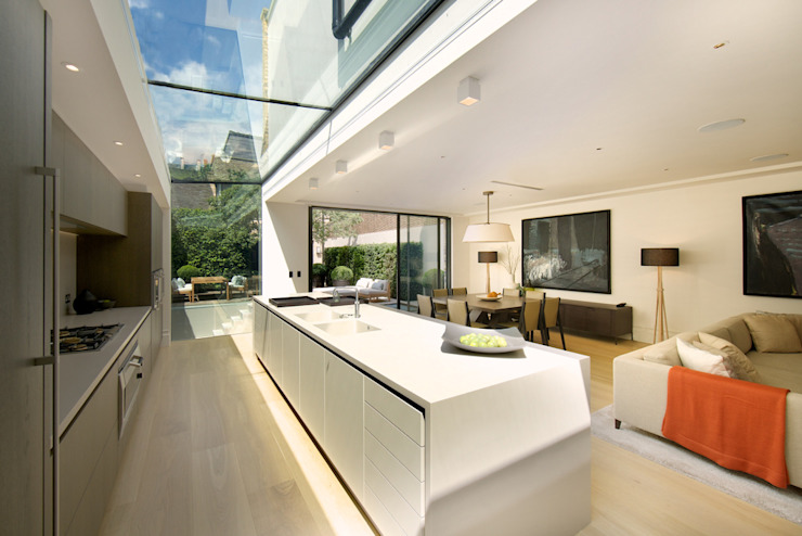​Kitchen and sitting area with views of the back garden at Bedford Gardens house. Nash Baker Architects Ltd Cucina moderna Vetro Bianco