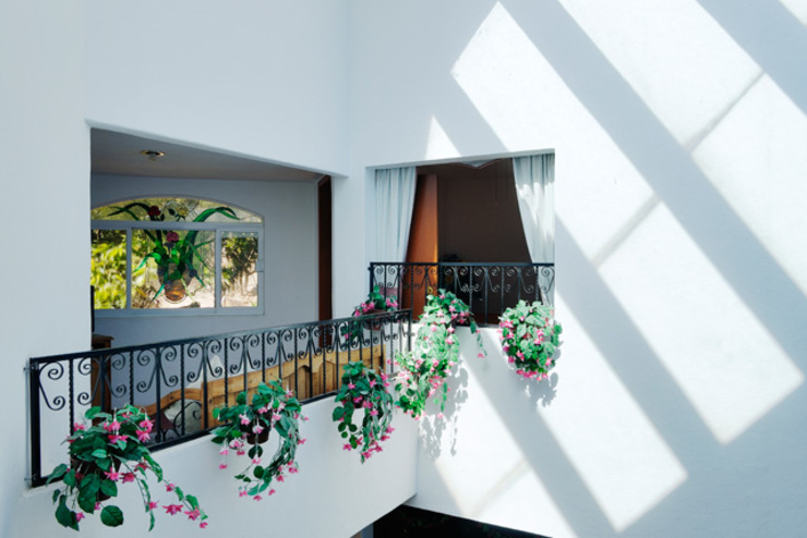 pasillo con vista ala doble altura Pasillos, vestíbulos y escaleras de estilo colonial de Excelencia en Diseño Colonial Hierro/Acero
