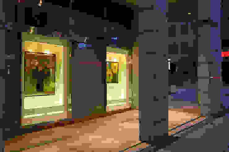 薬局 外観部分(通りに向けた画廊風ディスプレイ 絵画 夕方) モダンな医療機関 の 吉田設計+アトリエアジュール モダン