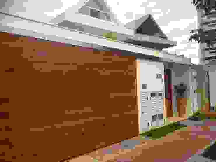 Portão da garagem deslizante em madeira. Garagens e edículas tropicais por Studio HG Arquitetura Tropical