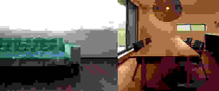 鮮やかなブルーのソファーとブラックチェリーのテーブル: 株式会社 kannaが手掛けた現代のです。,モダン