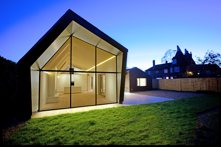 Rear elevation of ​Bourne Lane eco-house in Kent at twilight Case moderne di Nash Baker Architects Ltd Moderno Vetro
