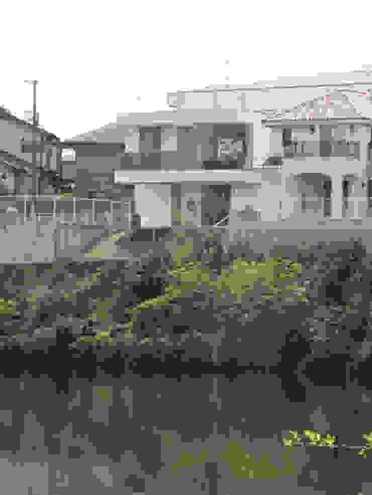 家の裏にある池越し モダンな 家 の atelier m モダン