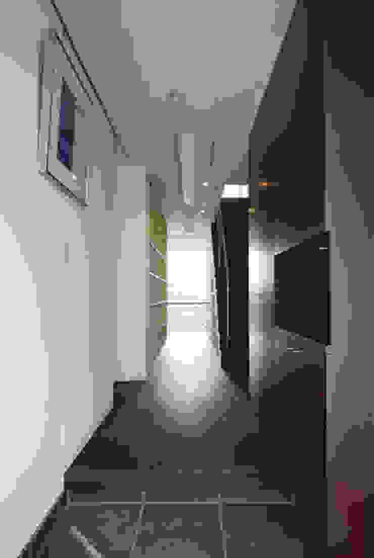 廊下の先にある本棚と書斎 モダンスタイルの 玄関&廊下&階段 の atelier m モダン