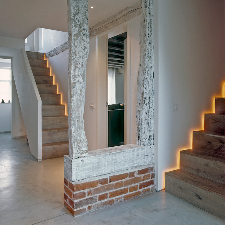 The hallway and stairs at ​the Old Hall in Suffolk Corredores, halls e escadas modernos por Nash Baker Architects Ltd Moderno Madeira Acabamento em madeira