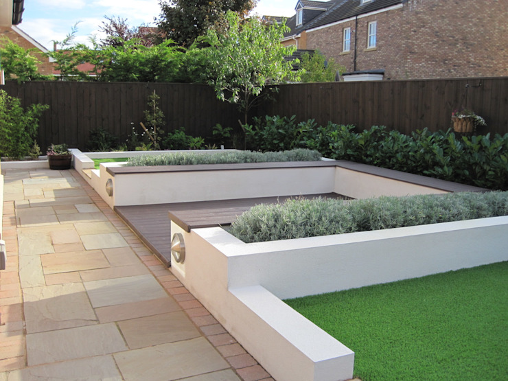 Contemporary rear garden with composite decking and artificial grass as view 1 but hedge more established:   by Mike Bradley Garden Design,