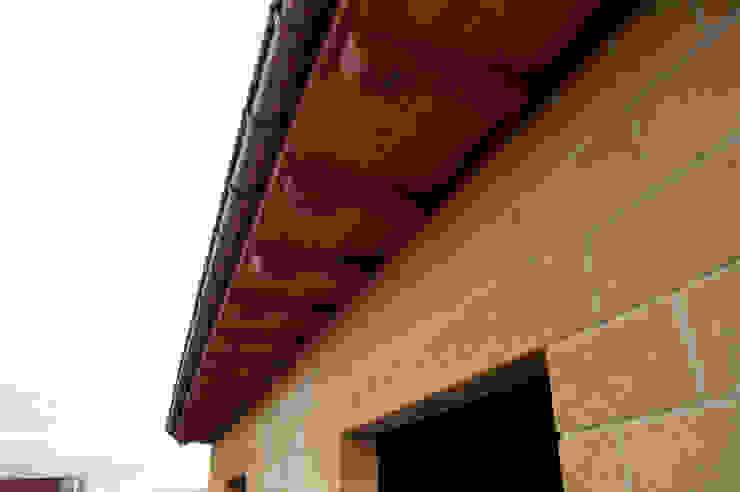 Alero con panel sandwich de madera con núcleo aislante y acabado decorativo en friso abeto barnizado panelestudio. panelestudio Paredes y suelos de estilo mediterráneo