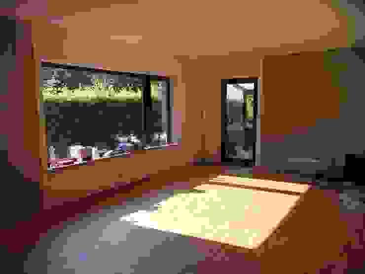 Das Wohnzimmer erhielt sandfarbene Wände und ebenso den Industrielamellenholzboden. Moderne Wohnzimmer von Grandi+Lutze Modern