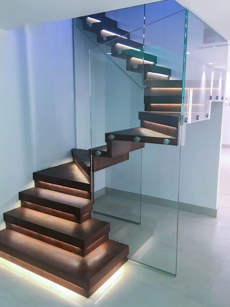 Elegant zig-zag staircase features walnut-clad treads and risers. Railing London Ltd Modern corridor, hallway & stairs