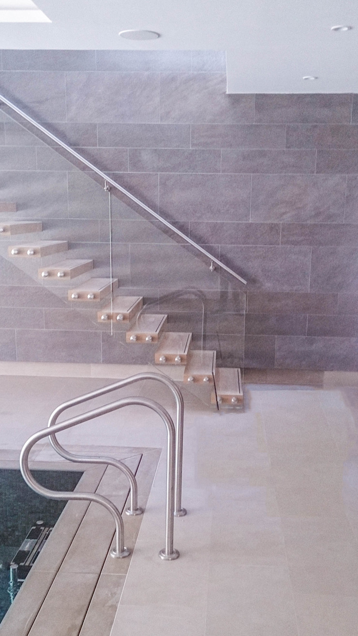 A custom-made floating staircase with oak-clad treads, a clear-glass balustrade and a wall-mounted stainless steel handrail. by Railing London Ltd Сучасний