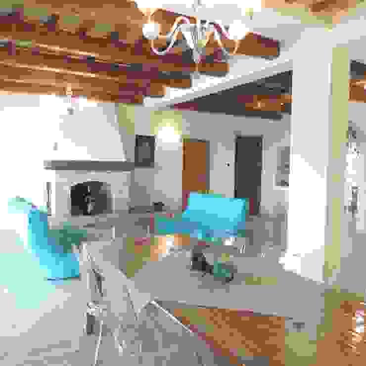 Ampio salotto con divani molto colorati e moderni in contrapposizione ad un ambiente rustico Soggiorno in stile rustico di Nadia Moretti Rustico