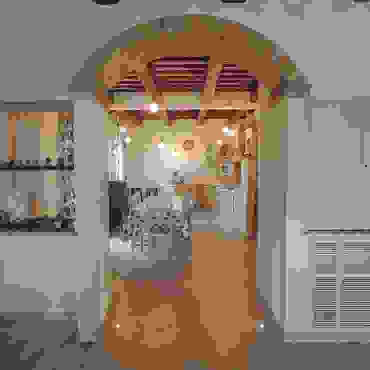 Veduta d'accesso alla grande cucina con illuminazione a pavimento, lampade a sospensione e nicchie passanti per un ampio spazio Cucina in stile rustico di Nadia Moretti Rustico