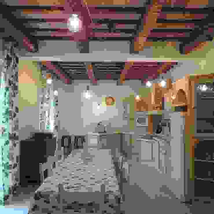 Cucina rustica murata con piano piastrellato e ante in legno verniciato e invecchiato. Le lampade a sospensione danno più risalto alla travatura Cucina in stile rustico di Nadia Moretti Rustico