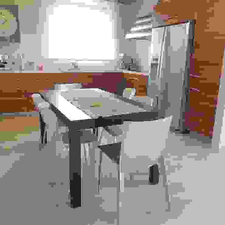 Cucina moderna in legno con frigo americano, cappa in acciaio e tavolo da pranzo Cucina moderna di Nadia Moretti Moderno