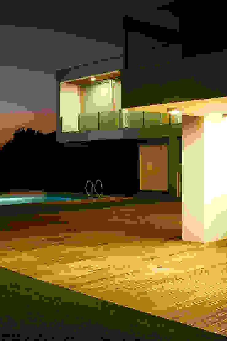 Vista nocturna do exterior com a piscina Casas modernas por Central Projectos Moderno