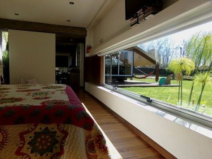 Casa de madera en VILLA ELISA – La Plata Dormitorios rústicos de juan olea arquitecto Rústico