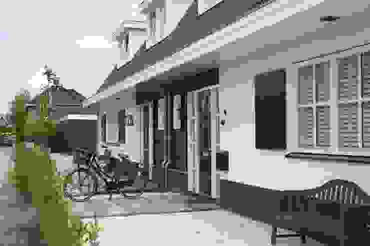 Landelijke woning met wit gevelstucwerk en zwart potdekselwerk.:  Huizen door Brand BBA I BBA Architecten