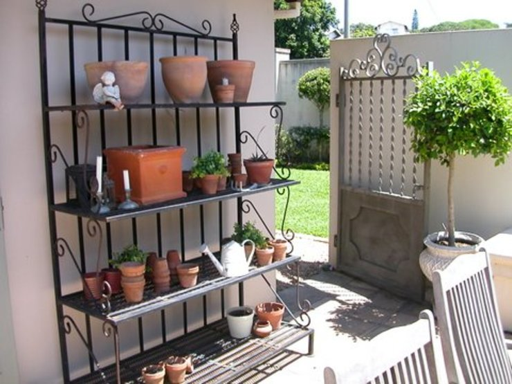 A delicate herb rack in the French courtyard: classic  by Finely Found It Interiors, Classic Iron/Steel