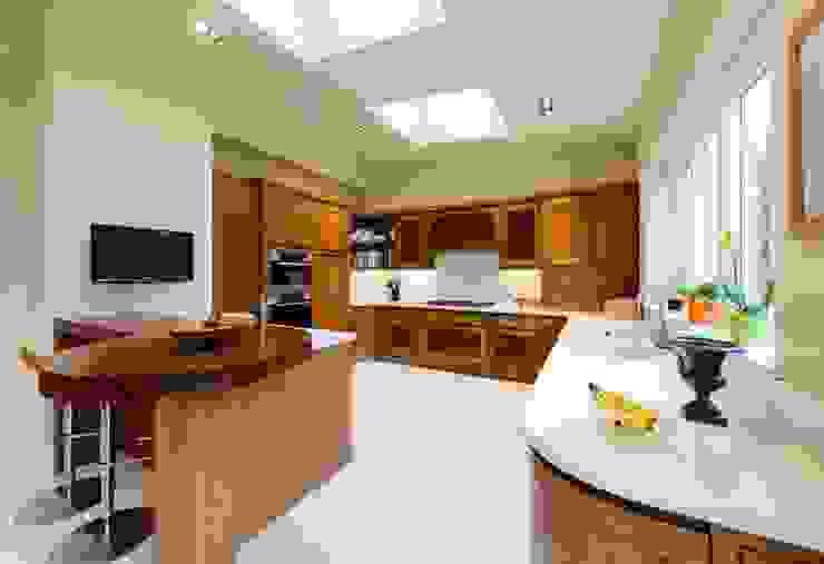 Walnut Curved Kitchen with White Corian Worktops od George Bond Interior Design Nowoczesny