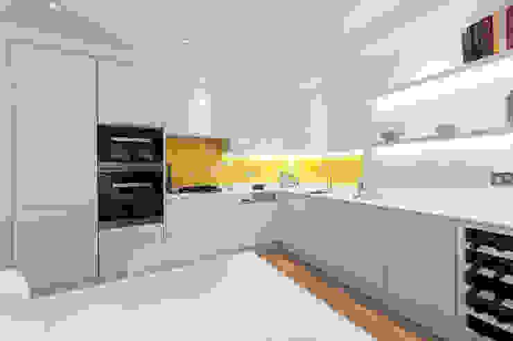 White contemporary kitchen with yellow glass splashbacks and herringbone wood floor Minimalist kitchen by Timothy James Interiors Minimalist Wood Wood effect