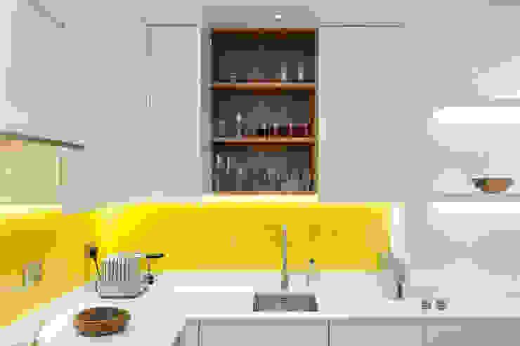 White contemporary kitchen with yellow glass splashbacks and herringbone wood floor Minimalist kitchen by Timothy James Interiors Minimalist Glass