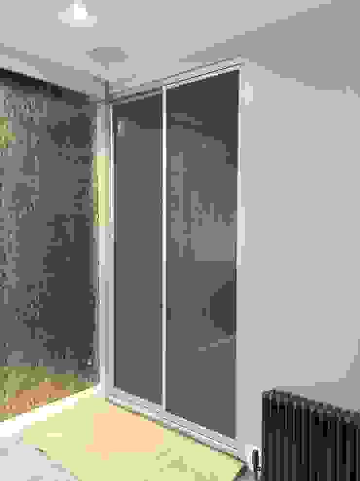 Tinted frosted glass sliding door wardrobe for cinema room. Sliding Wardrobes World Ltd Sala multimediaMuebles