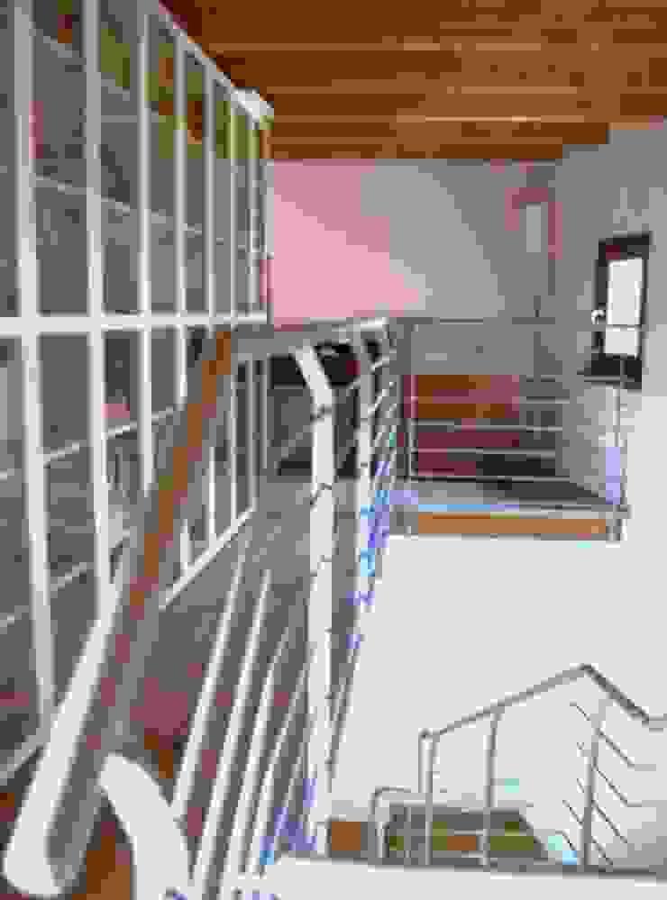 Ballatoio con libreria e angolo lettura Sala multimediale moderna di Studio d'Architettura TAUNISIO Moderno Metallo