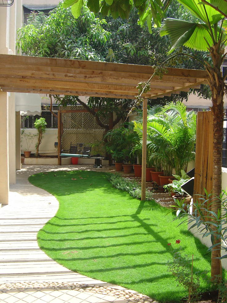 Lawn area with pergola Tropical style garden by Land Design landscape architects Tropical