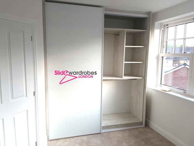 Floor to ceiling wardrobe with 2 sliding doors. Opened door view Oleh Slide Wardrobes London Minimalis Kaca