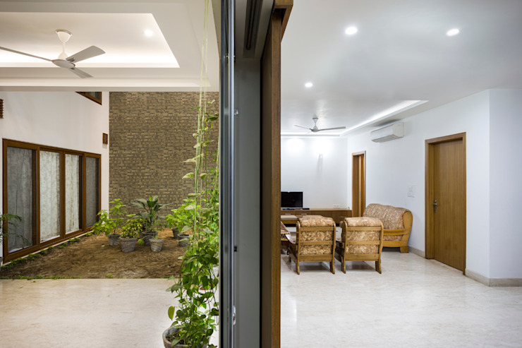 Living and Dining Space of the house at equilibrium with the internal courtyard. Country style living room by Manuj Agarwal Architects Country