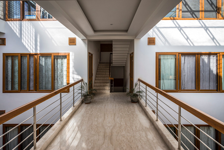 Bridge overlooking the courtyard on either side Modern corridor, hallway & stairs by Manuj Agarwal Architects Modern